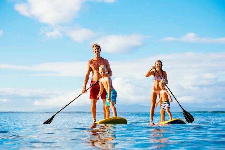 A family paddle-boards near Ocean Isle Beach