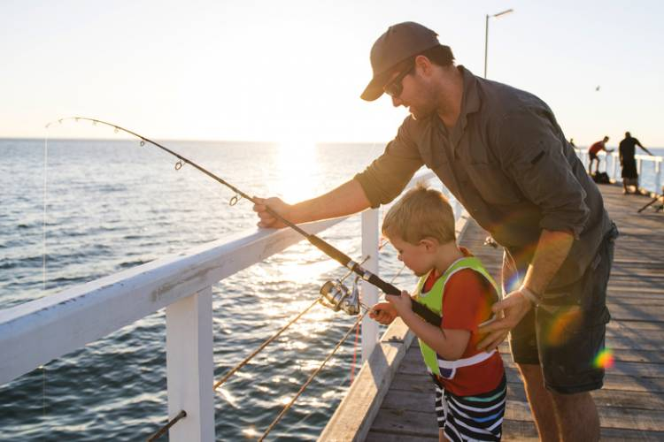 A father and son fish on a pier